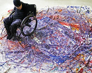 MADELYN P. HASTINGS | THE VINDICATOR  Jeff Sanders uses his wheelchair to make a painting. He will sell it in a couple of months and donate money to the  Warren Family Mission. He's a recovering addict himself and has been staying at the mission.