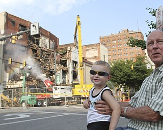 William D. Lewis\The Vindicator.Loren Kindler and his grandson Clark McAllen, 2, watch demolition of the Paramount Theater in downtown Youngstown 7-9-13. Kindler's father worked in the building.