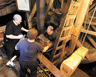 David Siembieda, owner of All-Do-It Technical Services LLC of Youngstown, hands up a piece of a beam being removed from Mill Creek Park's Lanterman's Mill to his workers, Gary Kaszowski, in background, and Joe Oates on Tuesday. The new support beam for the water wheel hangs from the chain at right, ready to be installed.