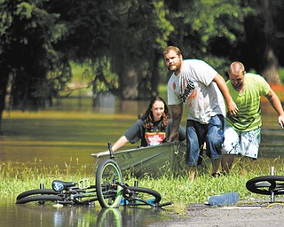 From left, Shelby Bosley, Jeff Reider and Jake Henry of Leavittsburg pull their canoe to dry land on Meadowbrook Drive on Thursday as they help evacuate residents from low-lying areas of Leavittsburg.