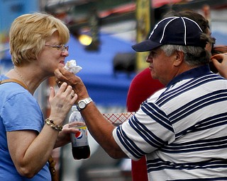 MADELYN P. HASTINGS | THE VINDICATOR  Fred Hunsinger of Canfield helps his wife, Sue, by wiping barbecue sauce off her face at the Eastwood Rib Fest in Niles on Saturday, July 20. The event runs through Sunday.