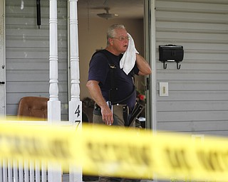 MADELYN P. HASTINGS | THE VINDICATOR  Campbell firefighter Eugene Skelley wipes off his face on the porch of 47 7th Street where a 5 victim shooting and fire occurred on Saturday, July 20.