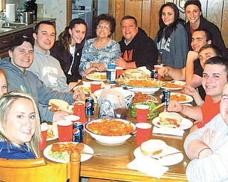 Special to The Vindicator: Surrounding Carol DiFabio (top center) at one of the Italian feasts she prepares each week for her family are, from left, Briana DeRose, niece; Alisa Rasoth, family friend; Mike DeRose, nephew; Vincent Morocco, grandson; Gia DiFabio, granddaughter; Mike DiFabio, her son; Tori Murray and Jami DeFabio, granddaughters; Geno DeFabio, nephew; John Morocco and Mike DeFabio, grandsons; and Billy Stoy, friend.