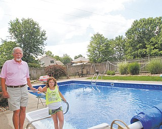Joseph Bettura of Mayflower Drive, Boardman, and his granddaughter, Livia, 11, stand by Bettura's in-ground swimming pool. The Ohio Edison Co. has sued Bettura and his wife, Marsha, to recover the cost of raising the utility's high-voltage transmission lines to a safer height above the pool.