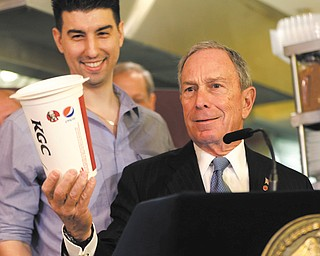 New York City Mayor Michael Bloomberg looks at a 64-ounce cup, as Lucky's Cafe owner Greg Anagnostopoulos, stands behind him. An appeals court ruled Tuesday that New York City's Board of Health exceeded its legal authority and acted unconstitutionally when it tried to put a size limit on soft drinks served in city restaurants.