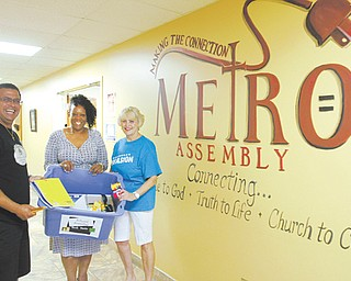 "Supporters of the Goodness Invasion, planned Aug. 10 at the Covelli Centre in Youngstown, show a sampling of some of the school supplies being collected to distribute at the event. From left are Pastor Rafael Cruz of the Jericho Project and Unity Baptist Church in Boardman; Kathy Hammond, president of Finer Things Academy, which is a co-sponsor of a ""Let's Move"" block party planned the same day downtown; and Anita Oles, food pantry coordinator of God's Warehouse at New Life Church in Poland."