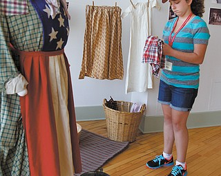 Alina Taylor, 13, of Boardman looks at Civil War-period costumes. This week, Alina is participating in the Mahoning Valley Historical Society's Turning Points Civil War Summer Day Camp.