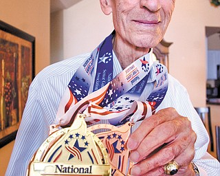 Bessemer, Pa., native Joe Tiratto, 87, wears the medals that he won while competing in the 2013 National Senior Games, which took place July 19-Aug. 1 in Cleveland. Tiratto's haul included a gold medal in singles pickleball, a bronze in mixed-doubles pickleball and a bronze in singles bocce.