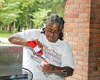 MADELYN P. HASTINGS | THE VINDICATOR..Anita Davis of Youngstown tops off a snowcone with flavor at the Youngstown National Night Out at Wick Park on August 6, 2013. This is part of National Night Out program, dedicated to the development and promotion of various crime-prevention programs including neighborhood watch groups, law enforcement agencies, state and regional crime prevention associations, businesses, civic groups, and individuals, devoted to safer communities..... - -30-..