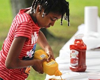 MADELYN P. HASTINGS | THE VINDICATOR..Seairra Brady, 6, of Youngstown tops her hot dog with mustard at the Youngstown National Night Out at Wick Park on August 6, 2013. This is part of National Night Out program, dedicated to the development and promotion of various crime-prevention programs including neighborhood watch groups, law enforcement agencies, state and regional crime prevention associations, businesses, civic groups, and individuals, devoted to safer communities.... - -30-..