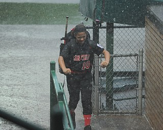 Canfield player #10 Sydney Fabry sprints for protection from the rain after grabbing her equipment from the dugout.