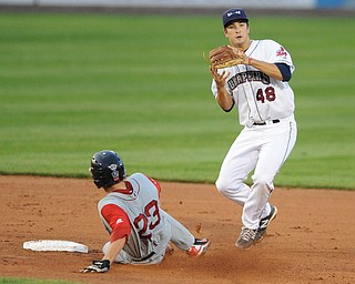 Scrappers infielder #48 James Roberts jumps in the air after stepping on second base after stepping on second base to force out Lowell base runner #23 Danny Bathea. The throw to first base would not be in time to first.