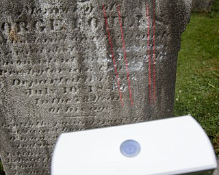 MADELYN P. HASTINGS | THE VINDICATOR  Matt O'Mansky is using a 3-D scanner to try to make out the words on a very old eroded tombstone in the Glenview Cemetery in East Palestine. O'Mansky  was contacted by a descendant of George Foulkes, who the tombstone is dedicated to. Foulkes was captured by Indians as a young boy in 1780 and remained a captive for 11 years before escaping.