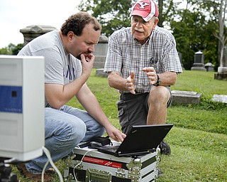 MADELYN P. HASTINGS | THE VINDICATOR  (L-R) Matt O'Mansky and Tom Delvaux look at the results of a 3-D scan of the eroded tombstone of George Foulkes. O'Mansky is using the scanner to try to make out the words on the tombstone in the Glenview Cemetery in East Palestine. O'Mansky  was contacted by Jerry Ward, who is a descendant of Foulkes. Foulkes was captured by Indians as a young boy in 1780 and remained a captive for 11 years before escaping.