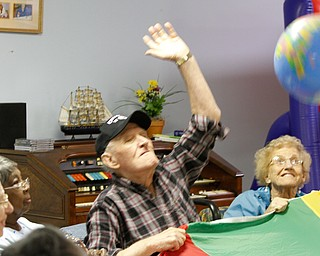 ROBERT K. YOSAY  | THE VINDICATOR  Joe Bartos swats at the beach ball as  Juanita Burg looks on---y  Senior Independence Adult Day Care 1393 Boardman Canfield Rd is the new digs for the people who used to be clients at the Mahoning County Adult Day Care Program.