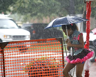 MADELYN P. HASTINGS | THE VINDICATOR  Camryn Stewart, 9, of Warren runs through the rain before her performance with Natalie's Dance Company at the Warren Italian Festival on Thursday, August 8. The festival runs through Sunday.