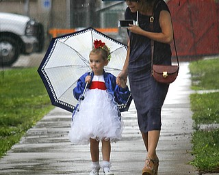 MADELYN P. HASTINGS | THE VINDICATOR  (L-R) Sadee Zamarelli, 4, and her aunt Maureen of Warren try to stay out of the rain that delayed the Warren Italian Festival on Thursday, August 8. Sadee participated in the Miss Italian Pageant. The festival runs through Sunday.