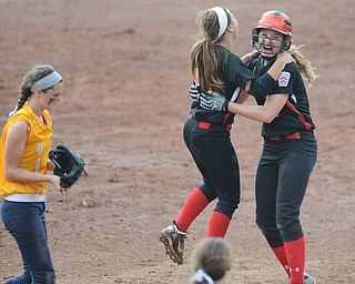 Canfield batter #2 Maddy Johns gets a hug from teammate #21 Ellie Dundics after knocking in the game winning run in the bottom of the 8th inning. Michigan player #4 Maddie Bell walks across the infield.