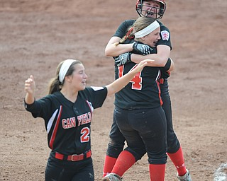 Canfield player #2 Maddy Johns gets a hug from teammate #14 Jenna Gibson after knocking in the game wining hit while #21 Ellie Dundics walks around the infield in disbelief.