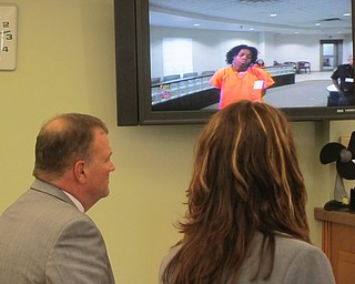 Atty. Mark Hanni, left, stands before a video monitor in Warren  