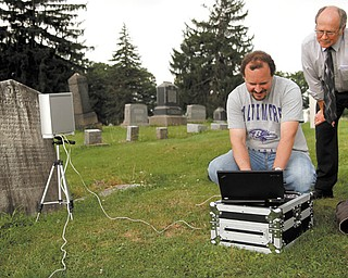 Matt O'Mansky, left, a Youngstown State University associate professor, and Jerry Ward look at the results of a scan from the eroded tombstone of George Foulkes. O'Mansky is using the scanner to try to make out the words on the tombstone in Glenview Cemetery in East Palestine.