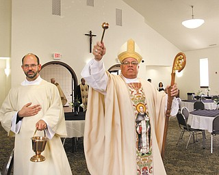 Bishop George V. Murry of the Diocese of Youngstown sprinkles holy water in the new parish center of St. Dominic Church, 77 E. Lucius Ave., Youngstown, during a dedication Thursday. Assisting is Deacon John Ettinger.