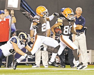 The Browns' Travis Benjamin (80), escorted by teammate Trevin Wade (26), eludes the Rams' Mike McNeill and returns a punt 91 yards for a touchdown in the second quarter of a preseason NFL game Thursday in Cleveland. The Browns won 27--19.