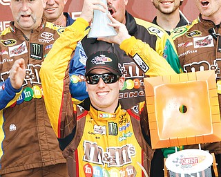 Kyle Busch celebrates in Victory Lane on Sunday after holding off Brad Kelselowski to win the Cheez-It 355 at The Glen in Watkins Glen, N.Y.