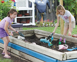 "Addison, 7, and Taylor Bycroft, 10, both of East Palestine, play in the ""dig area"" of the Family Garden at Mill Creek MetroParks' Fellows Riverside Gardens. The Family Garden is a priority for expansion under the master plan, or Gardens Northwest Project."