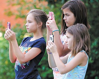 A historic moment is captured by students and neighbors Sarah Barriner, 10, left, Hannah Antal, 10, and Hayley Antal, 8, as they each took a picture of the Idaho Road ribbon-cutting Monday with their cellphones.