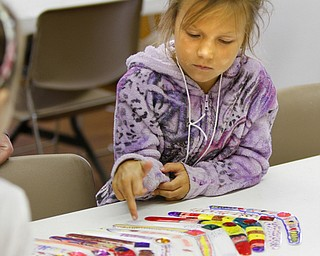 Zoey Schineiter, 8, of Austintown ponders the designs on boomerangs she and other children decorated as part of AgVenture Camp.