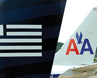 A US Airways plane, foreground, and an American Airlines plane are seen parked at the terminal at Washington's Ronald Reagan National Airport on Tuesday. The Justice Department and a number of U.S. state attorneys general Tuesday challenged a proposed $11 billion merger between US Airways Group Inc. and American