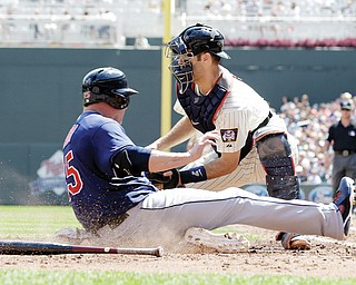 The Indians' Jason Giambi slides by Twins catcher Joe Mauer to score on a two-run single by Mike Aviles in the fourth inning of Wednesday's game in Minneapolis. Giambi connected for a three-run homer in the eighth, and