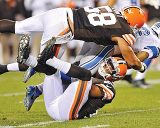 Browns cornerback Trevin Wade, bottom, brings down Lions wide receiver Terrence Austin with help from outside linebacker L.J. Fort (58) during the third quarter of a preseason NFL game at FirstEnergy Stadium in Cleveland. The Browns dominated the Lions 24-6.