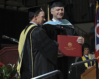 David Anney smiles after receiving his diploma (he was the first presentation of the day I believe a doctorate) while getting a hand shake from Scott Martin during the summer commencement ceremony Saturday morning at Beeghley Center.