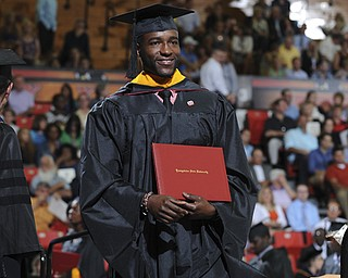 Omadee Curry smiles while walking across the stage after receiving his masters degree during the summer commencement ceremony Saturday morning at Beeghley Center.
