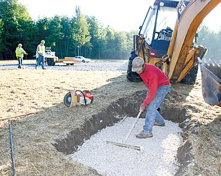 Workers with Miller-Young Paving of Bazetta, including Curtis Jones in the foreground, are shown at the new Eastlake MetroPark being created on state Route 46 just north of the Lake Vista retirement community in Cortland.