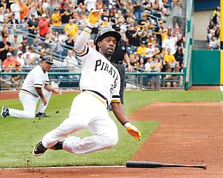 Pirates baserunner Andrew McCutchen slides home as he scores from first on a double by Russell Martin in the 