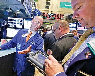 Specialist John O'Hara, left, works with traders at his post on the floor of the New York Stock Exchange. On Tuesday, the Dow Jones industrial average posted its fifth-straight day of losses, the first time that's happened this year.