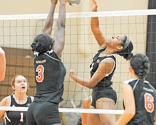 Girard's Alasjia Dykes, right, goes up for a spike as Howland's Kayla Manningham (3) attempts a block during a match Tuesday night a match at Howland High. Girard's Melanie Bakes (1) and Howland's Jessie Moore (6) watch. The Tigers outlasted the Indians in five games.