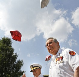 Admiral Kenneth Monroe Carr and Glenn Buzzard of Hubbard watch as star-shaped balloons are released during a service  at Windsor House at Liberty Arms to honor World War II veterans who never came home.