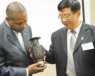 Warren Mayor Douglas Franklin, left, receives a vase as a gift from Xinghua Xuan, vice president of the Red Cross Society of China, Shandong Branch, during a reception for the Chinese delegation Thursday at the Mahoning County Emergency Management facility on Industrial Road in Youngstown.