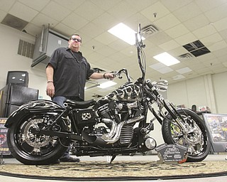 William D. Lewis\The Vindicator Dave Cook, owner of Sledgehammer Bobbers, poses with a custom motorcycle he built. His business is building an Evil Knievel tribute motorcycle..