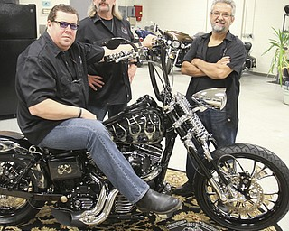 William D. Lewis\The Vindicator Dave Cook, left, owner of Sledgehammer Bobbers, poses with a custom motorcycle he built. His business, located in Howland, is building an Evil Knievel tribute motorcycle. With him are Dennis Markle, center, bike handler and detailer and George Beharry, head mechanic. William D. Lewis\The Vindicator.