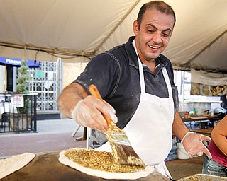 MADELYN P. HASTINGS | THE VINDICATOR..Elie Aboutouma of Lakewood makes a meat pie in the Oasis Bakery tent at the Arab American Community Festival in downtown Youngstown on Saturday, August 24, 2013.... - -30-..