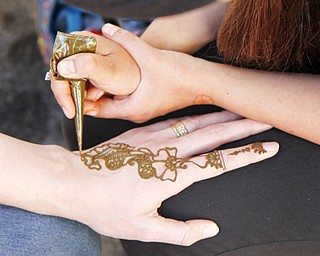MADELYN P. HASTINGS | THE VINDICATOR..Lamia Sassya of Boardman and 'Henna by Lamia' paints a henna tattoo on Dagmara Apaeva of Canfield at the Arab American Community Festival in downtown Youngstown on Saturday, August 24, 2013.... - -30-..