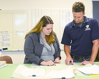 Chrystaline McArdle, left, from the planning committee, and Ryan Tekac, right, from the Board of Health, study a plat map in the planning commission in Austintown on Aug. 13.