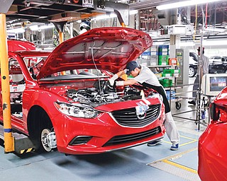 A Mazda employee works on the assembly line at the plant in Hofu, Yamaguchi Prefecture, southwestern Japan, on Tuesday. Mazda, the longtime also-ran of Japanese automakers, has a new super-efficient plant that's rolling off vehicles at a stunning rate of one every 54 seconds.
