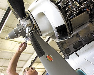Ron Butler, engine-shop supervisor for Winner Aviation, lubricates a propeller on a MU2 B40 aircraft at Youngstown-Warren Regional Airport in Vienna. Winner Aviation has been at the airport since the mid-1990s, and the staff performs myriad duties there.