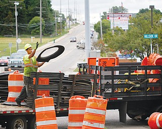 A worker sets up construction barrels along U.S. Route 224 and Hillside Drive in Canfield on Tuesday. The Ohio Department of Transportation will be resurfacing the road along 224 to Talsman Drive. The project should end in late October.